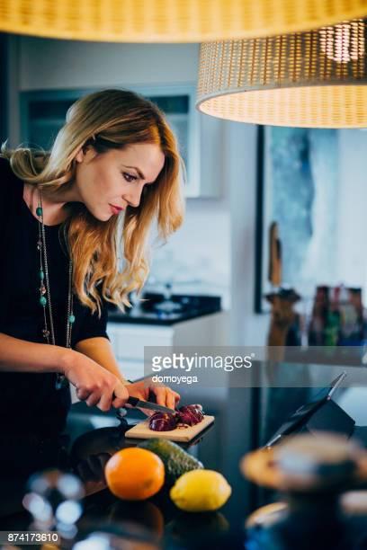 Mooie vrouw maken van gezonde maaltijd in de keuken