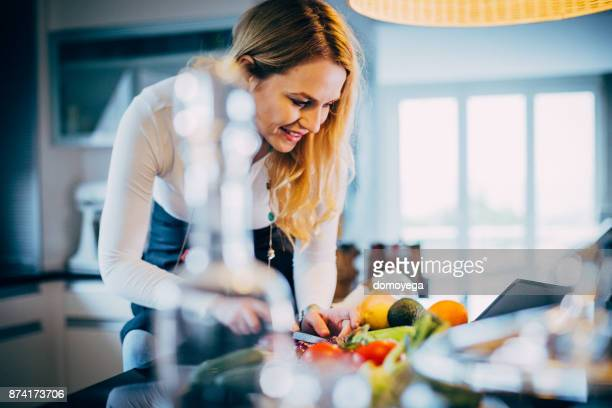 beautiful woman making healthy meal in the kitchen - low carb diet stock photos and pictures