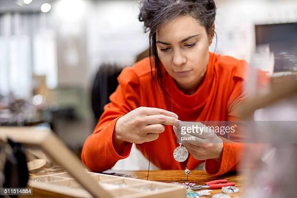 Beautiful woman making jewelry