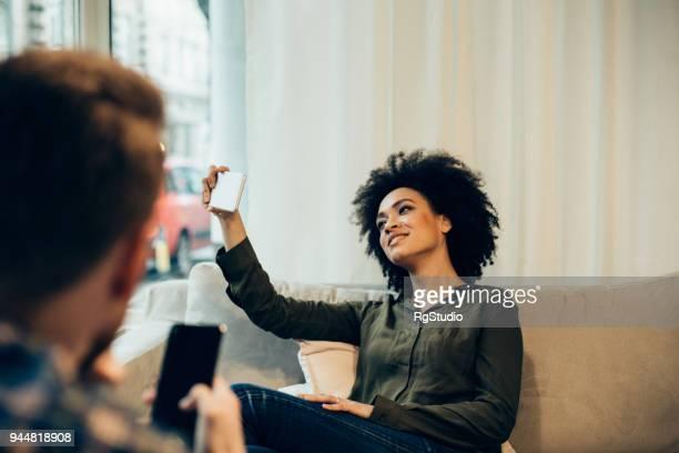 Beautiful woman making selfie in coffee shop