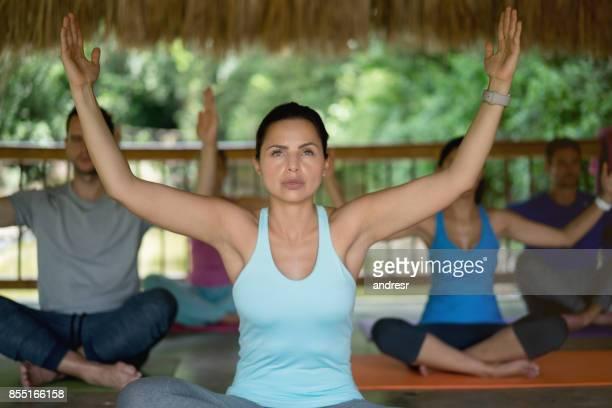 Beautiful woman meditating in a yoga class