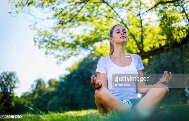 beautiful woman meditating in city park - good posture stock pictures, royalty-free photos & images