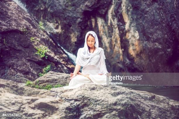 Beautiful Woman Meditating Outside Near Waterfall