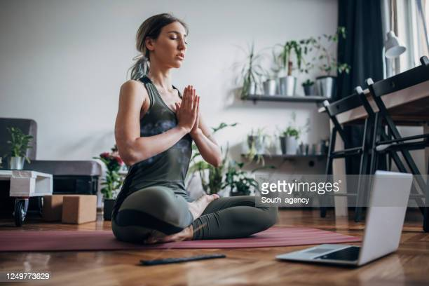 beautiful woman meditating with online guru - yoga stock pictures, royalty-free photos & images