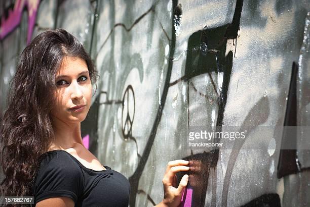 Beautiful woman model against graffiti wall background