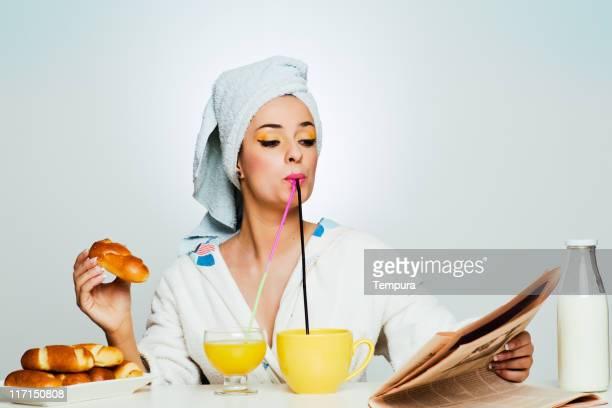 Bellissima donna multi-tasking la prima colazione.