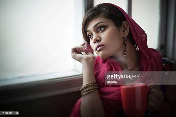 Beautiful woman near glass window at home with coffee mug.