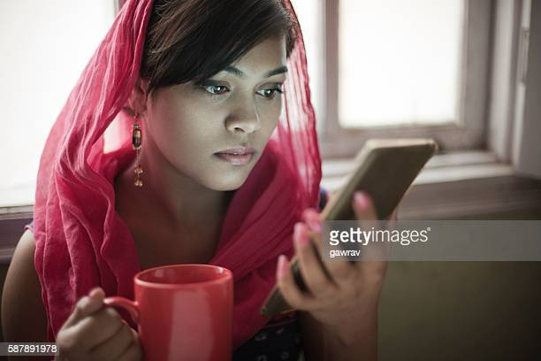 beautiful woman near window with coffee mug using smartphone. - dupatta stock pictures, royalty-free photos & images