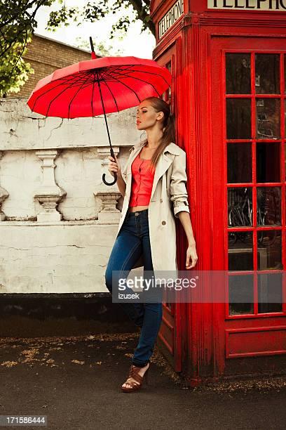 Schöne Frau neben Telefonzelle