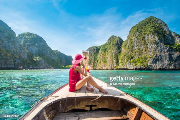 beautiful woman on a longtail boat in maya bay, phi phi islands, thailand. - phi phi islands stock-fotos und bilder