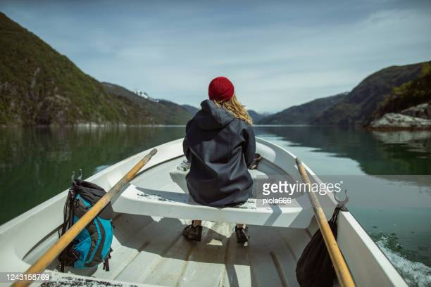 beautiful woman on a small fishing boat: sailing in a fjord in norway - vintage raincoat stock pictures, royalty-free photos & images