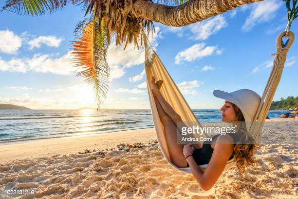 a beautiful woman on a tropical beach, sleeps in a hammock - vacances à la mer photos et images de collection