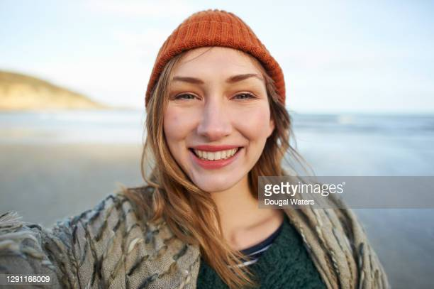 beautiful woman on autumn beach selfie. - dougal waters stock pictures, royalty-free photos & images