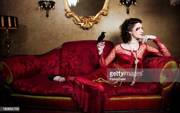 Beautiful Woman on Red Antique Couch with Black Bird