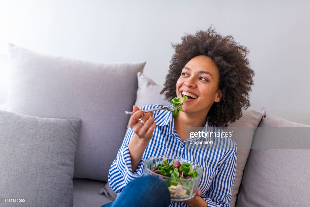 Beautiful woman on the sofa eating a healthy salad : Stock Photo