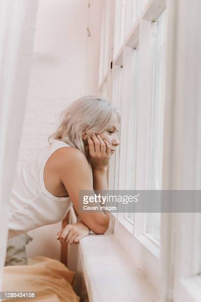 beautiful woman opening curtains and looking through the window - boredom stock pictures, royalty-free photos & images