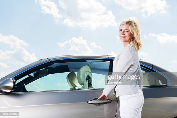 Beautiful woman opening her car door.