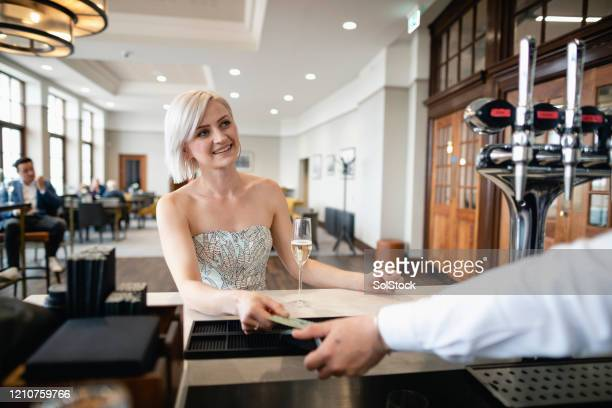 beautiful woman paying for champagne at bar - strapless stock pictures, royalty-free photos & images