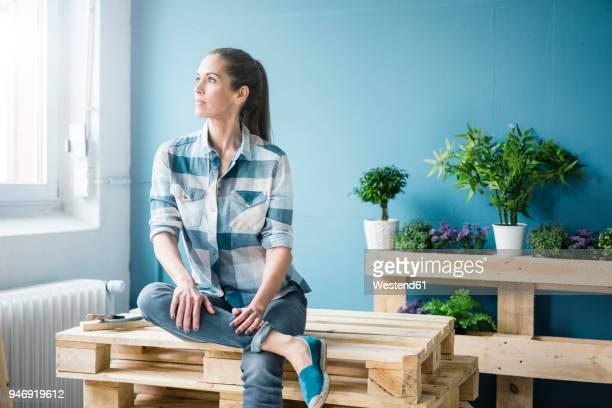 beautiful woman planning to refurbish her home with pallets - donne di età media foto e immagini stock