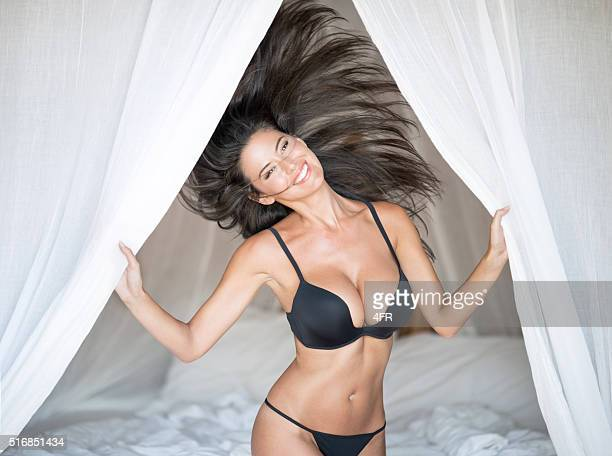 beautiful woman playful on vacation in bed - seductive women stock pictures, royalty-free photos & images