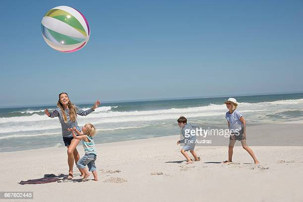 Beautiful woman playing beach ball with her children