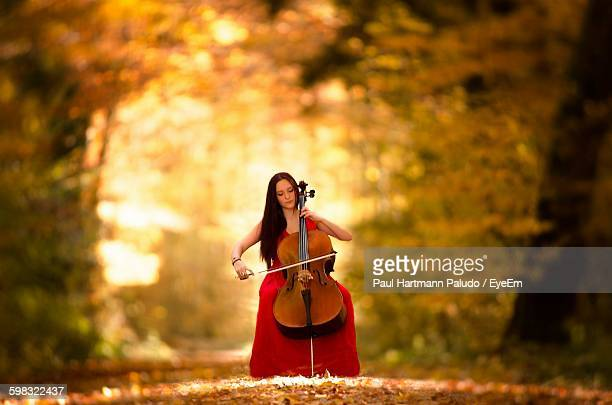 Beautiful Woman Playing Double Bass In Forest During Autumn