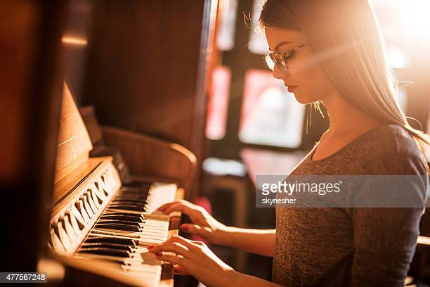 Beautiful woman playing old-fashioned piano.