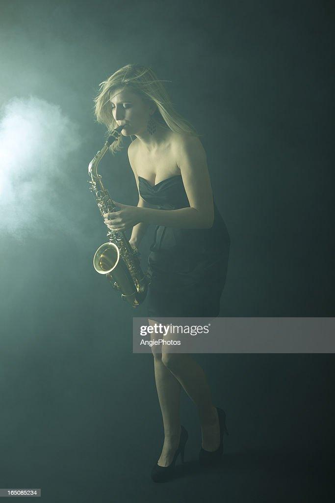 Beautiful woman playing saxophone : Stock Photo