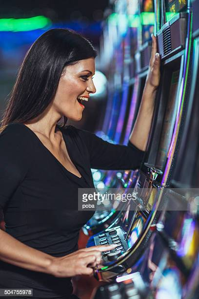 beautiful woman playing slot machine in the casino - coin operated stock photos and pictures