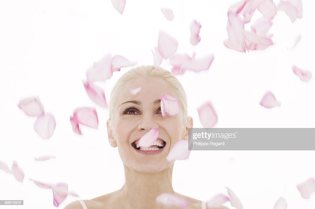 Beautiful woman playing with pink rose petals : Bildbanksbilder