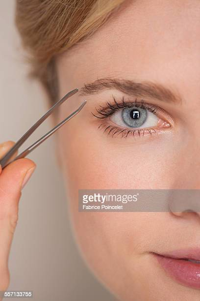 Beautiful woman plucking eyebrow with tweezers