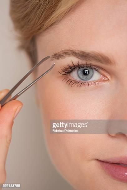 beautiful woman plucking eyebrow with tweezers - 修眉 個照片及圖片檔