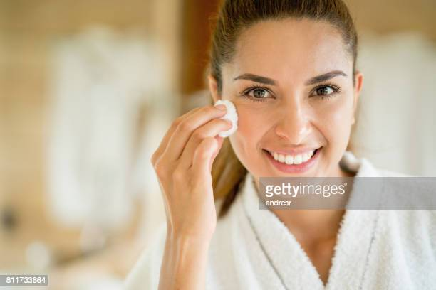 Beautiful woman portrait cleansing her face with a cotton bud
