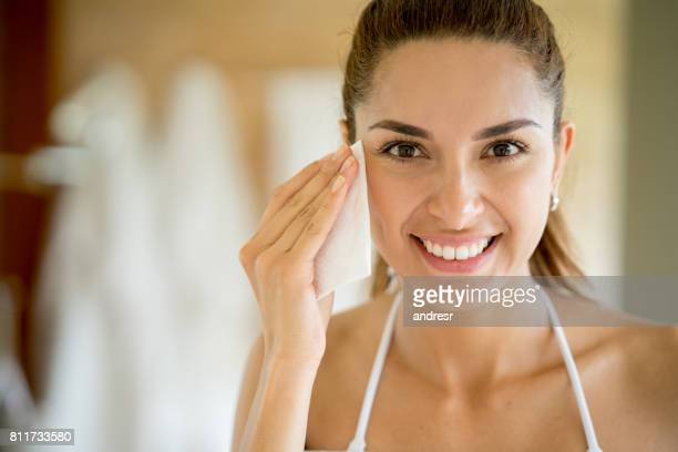 Beautiful woman portrait cleansing her face with a pad