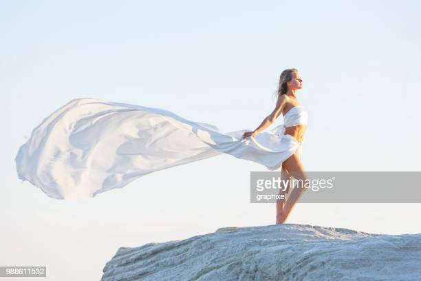 Beautiful Woman Posing With Fabric on the Rock