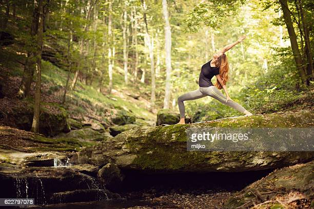Beautiful woman practicing yoga in nature