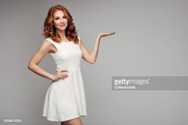 beautiful woman presenting a copyspace - dress stock pictures, royalty-free photos & images