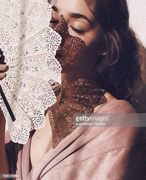 beautiful woman protecting herself from sunlight through hand fan - hand fan stock photos and pictures