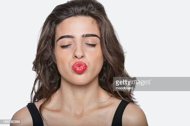 Beautiful woman puckering lips with eyes closed over gray background