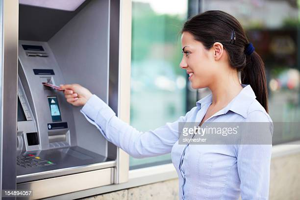 Beautiful woman puting her credit card at the ATM.