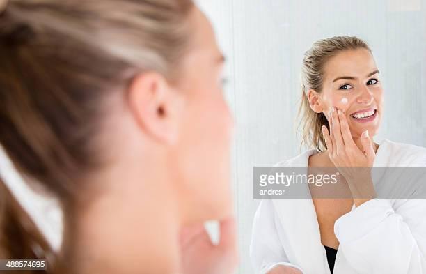 Beautiful woman putting cream