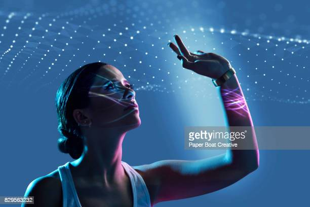 Beautiful woman reaching up to touch waves of tiny light beams in the air, shot against a blue background