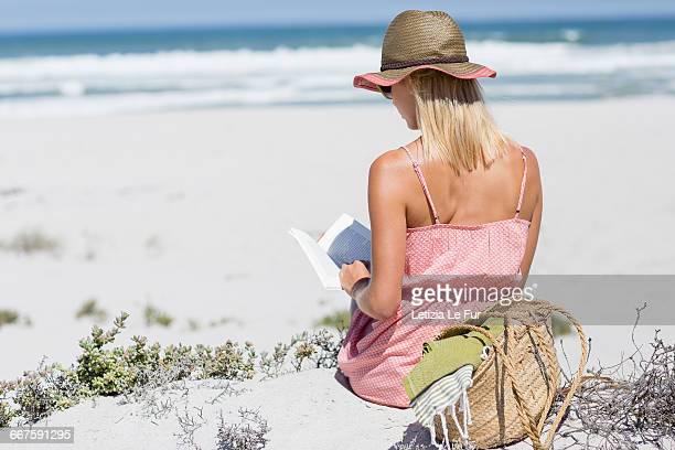 Beautiful woman reading a book o the beach