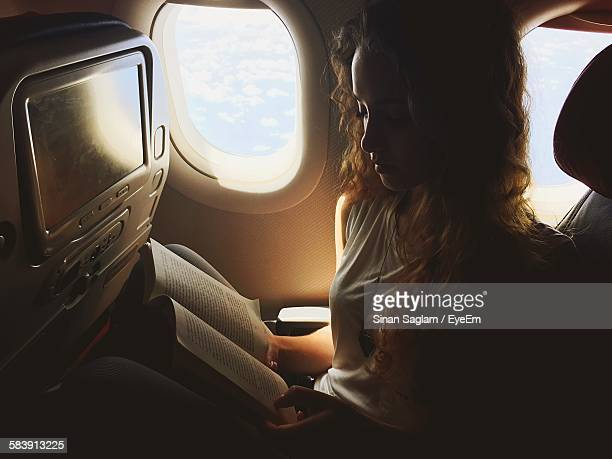 Beautiful Woman Reading Book In Airplane