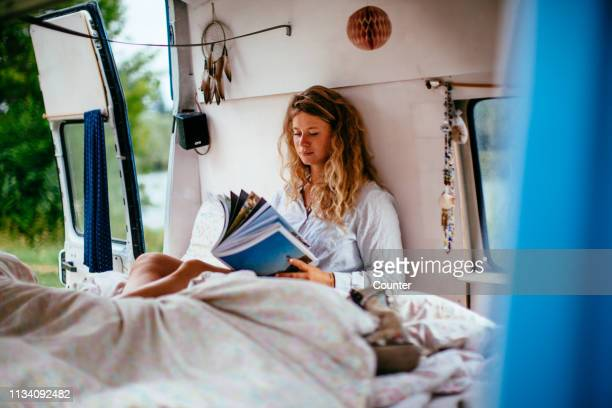 beautiful woman reading in camping bus - nature magazine stock pictures, royalty-free photos & images