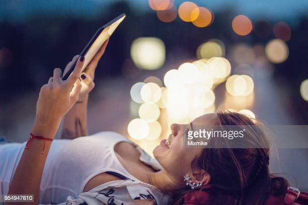 Beautiful woman reading on her tablet outdoors in the city