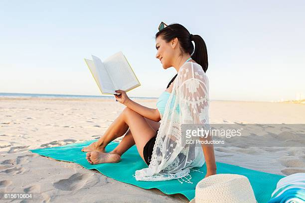 Beautiful woman reads a book on the beach