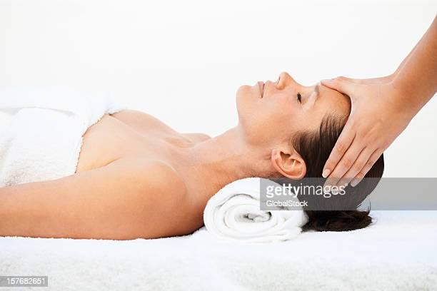 Belle femme à recevoir un massage de la tête contre blanc