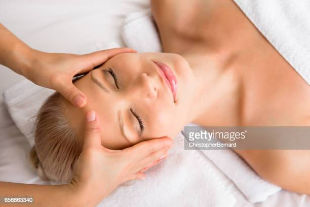 beautiful woman receiving head massage at spa - head massage stock photos and pictures