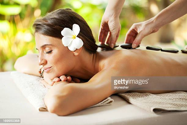 Beautiful woman receiving hot stone therapy.